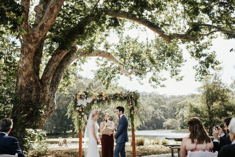 Outdoor Wedding Ceremony with Bride in Beaded Rosa Clara Wedding Dress and Groom in Navy Suit  Standing at the Floral Altar