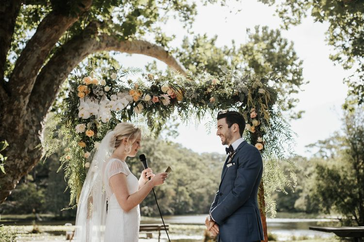 Outdoor Wedding Ceremony with Bride in Beaded Rosa Clara Wedding Dress and Groom in Navy Suit  Exchanging Vows in Front of Their Floral Arch Altar