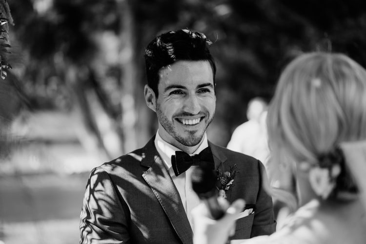 Groom in Bow Tie Smiling During Wedding Ceremony