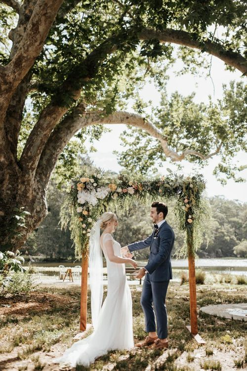 Bride in Rosa Clara Wedding Dress and Groom in Navy Suit Holding Hands in Front of Their Floral Arch Altar