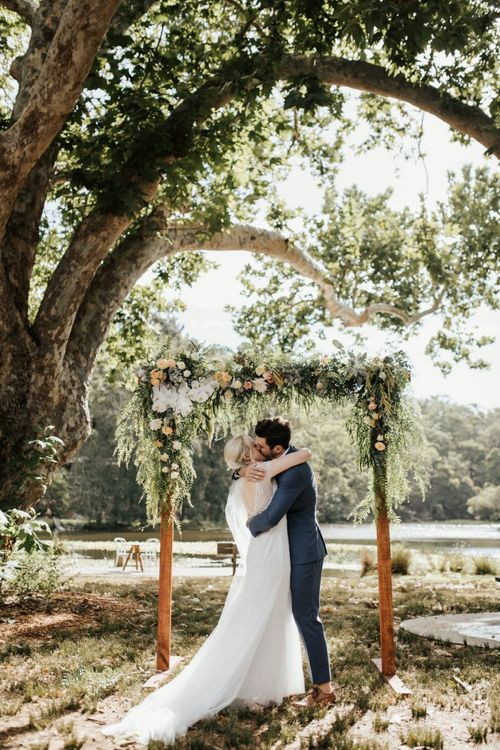 Bride in Rosa Clara Wedding Dress and Groom in Navy Suit Embracing in Front of Their Floral Arch Altar