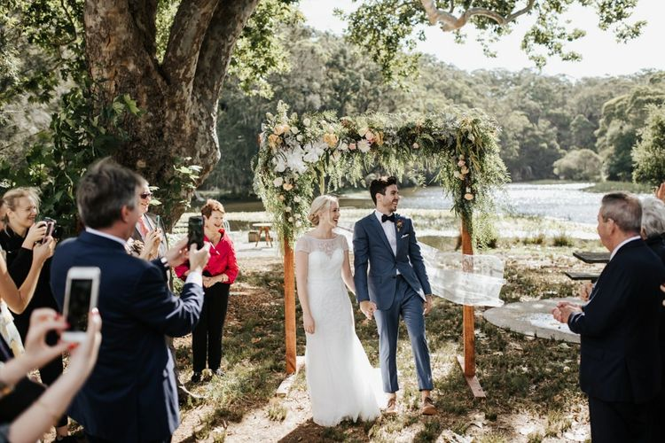 Bride in Rosa Clara Wedding Dress and Groom in Navy Suit Walking Up the Aisle