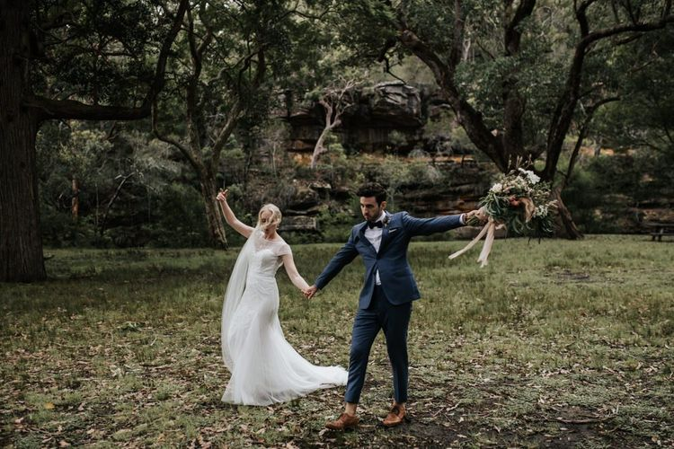 Bride in Rosa Clara Beaded Wedding Dress and Groom in Navy Suit with Bow Tie Skipping in the Bush