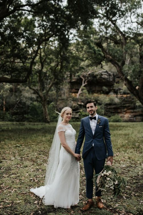 Bride in Rosa Clara Beaded Wedding Dress and Groom in Navy Suit with Bow Tie Holding Hands