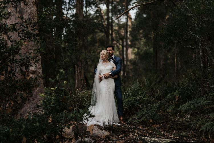 Bride in Rosa Clara Beaded Wedding Dress and Groom in Navy Suit with Bow Tie Embracing in the Woods