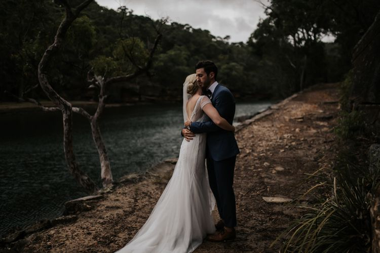 Groom in Navy Suit and bow Tie and Bride in Rosa Clara Wedding Dress Embracing by the Lake