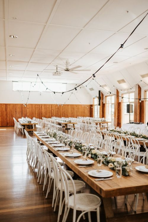 Wedding Reception Decor with Floral Table Runner and Festoon Lights