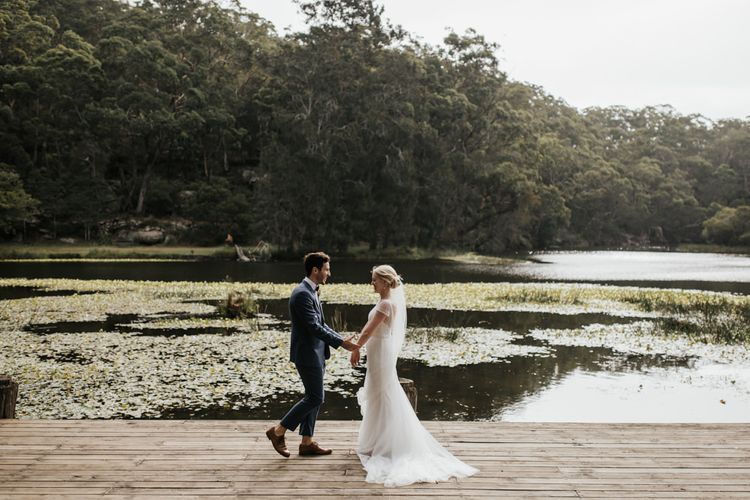 Bride in Rosa Clara Wedding Dress and Groom in Navy Suit by the Lake