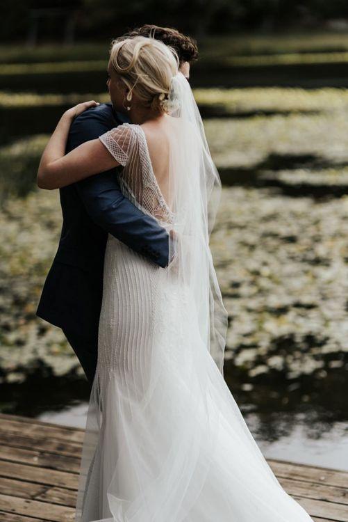 Groom in Navy Suit Embracing His Bride in beaded Rosa Clara Wedding Dress