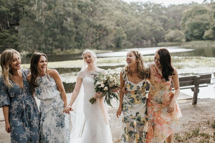 Bride and Bridesmaids Laughing by the Lake