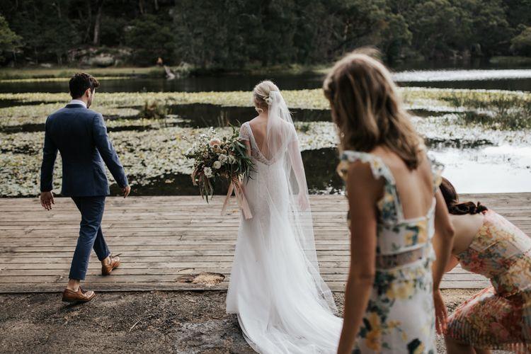 Bride and Groom Walking Towards the Lake