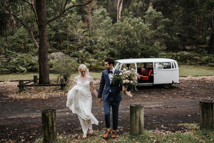 Bride in Rosa Clara Wedding Dress and Groom in Navy Suit Walking in the Woods