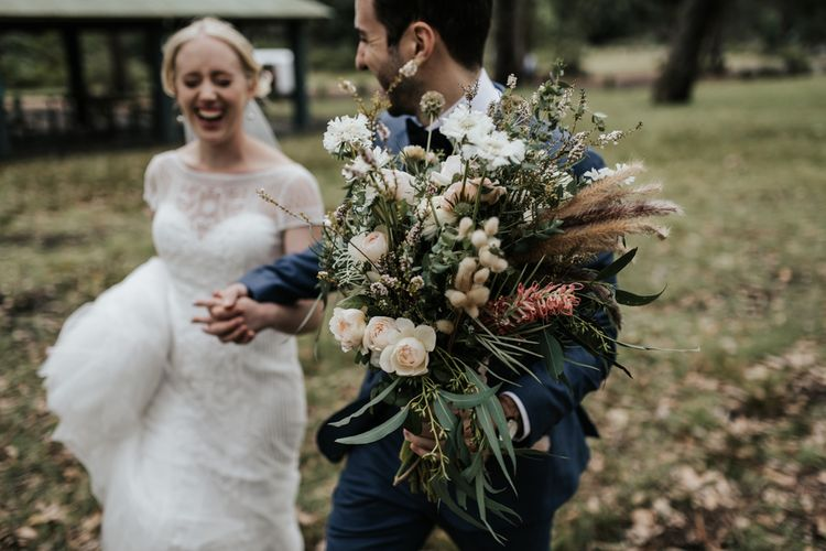 Groom Holding His Brides Hand and Her Pastel Oversized Wedding Bouquet