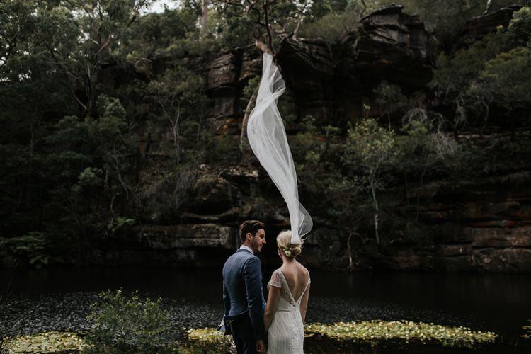 Groom in Navy Suit and Bride in Rosa Clara Wedding Dress and Flowing Wedding Veil