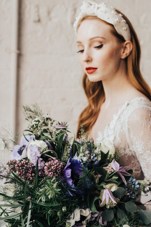Bride in Turban Headband, Red Lipstick and in Long Sleeve Lace Wedding Dress from Morgan Davies Bridal Holding a Lilac, White and Foliage Bouquet
