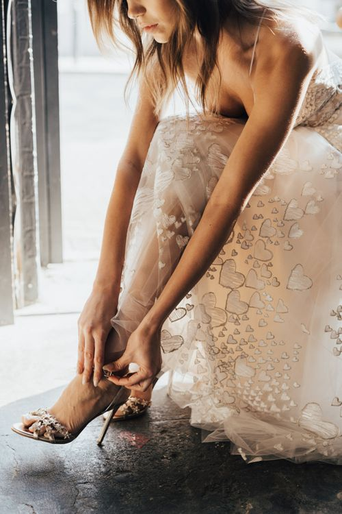 Bride Putting on Her Gold Strappy Shoes in a Heart Embroidered Wedding Dress from Morgan Davies Bridal