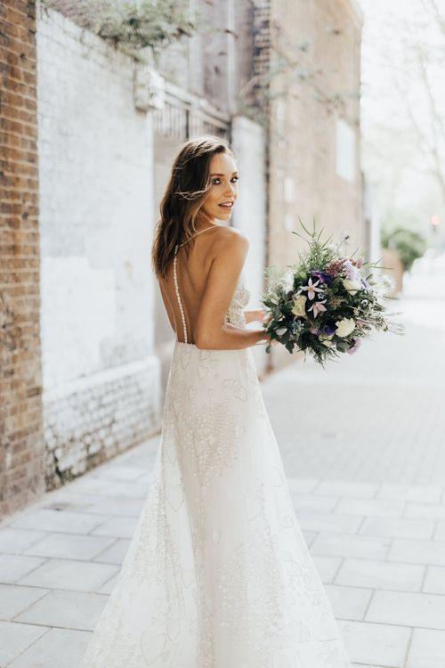 Bride in Heart Embroidered Wedding Dress with Illusion Back and Button Detail Holding a Bouquet of Lilac, White and Green Flowers