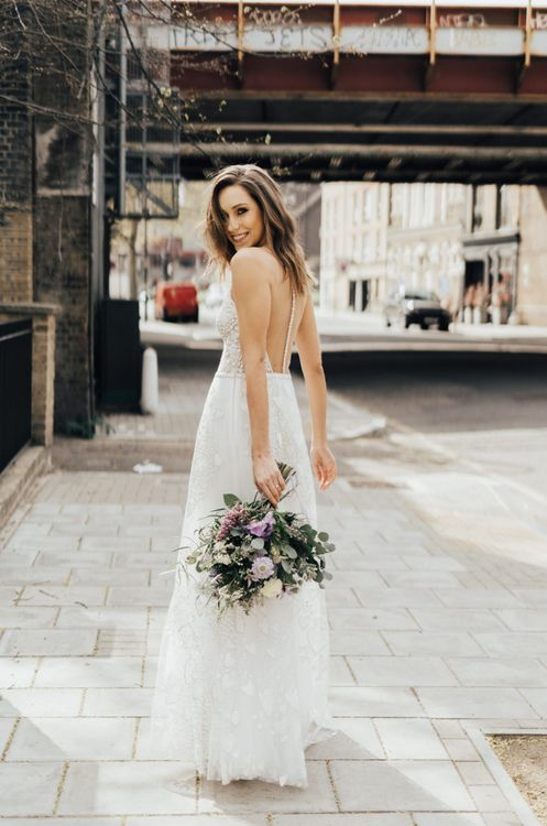 Bride in Heart Embroidered Wedding Dress with Illusion Back From Morgan Davies Holding a Lilac and White Wedding Bouquet