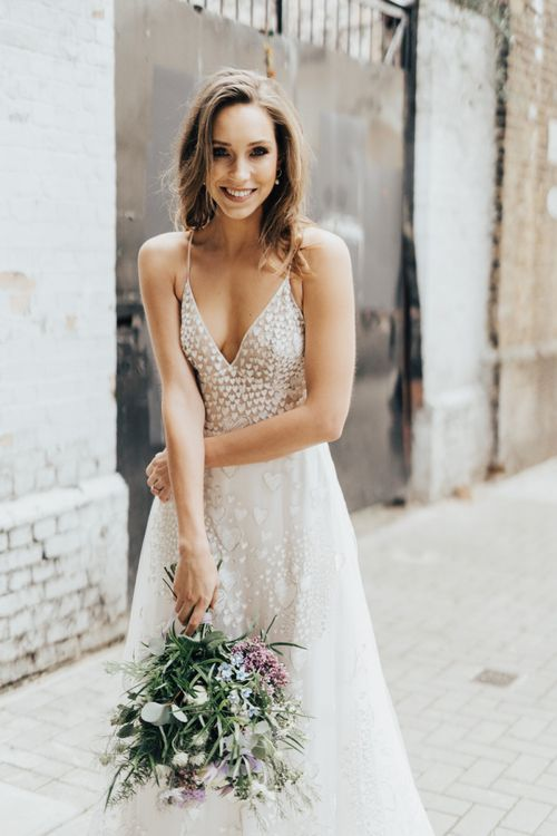 Bride in Heart Embroidered Wedding Dress with Spaghetti Straps From Morgan Davies Holding a Lilac and White Wedding Bouquet