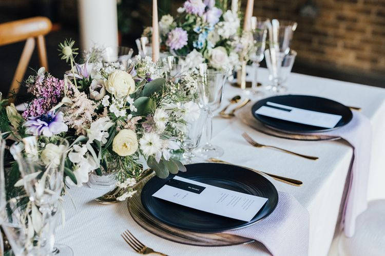 Tablescape with Monochrome Place Settings with Black Tableware, Gold Cutlery and Lilac and White Feminine Florals