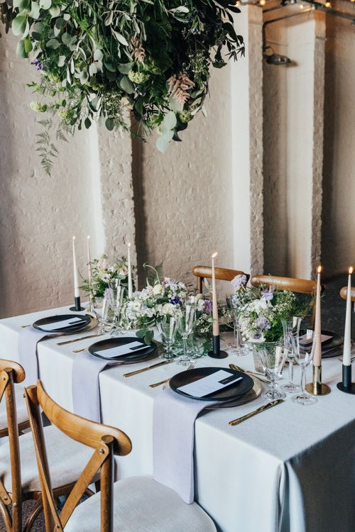 Elegant Tablescape Decor with Monochrome Place Settings with Black Tableware, Gold Cutlery, Taper Candles and  Lilac and White Feminine Florals