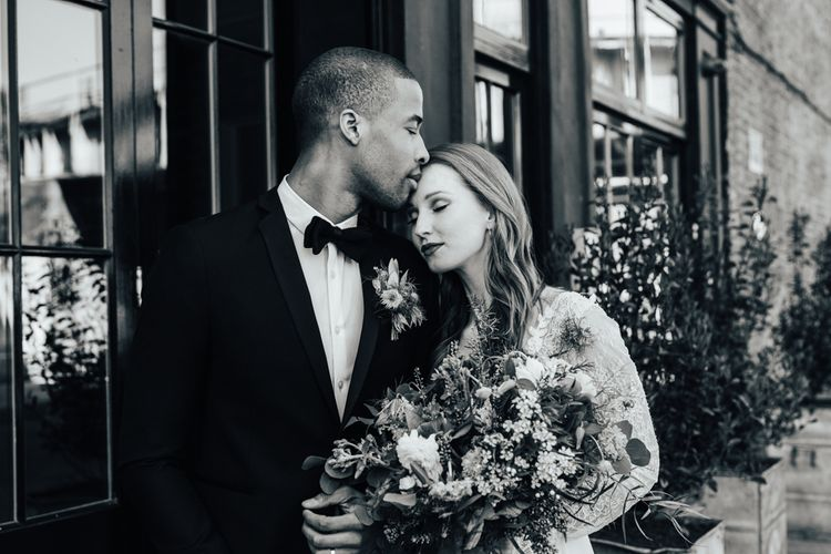 Groom in Black Tuxedo Kissing his Brides Head in a Lace Wedding Dress from Morgan Davies Bridal