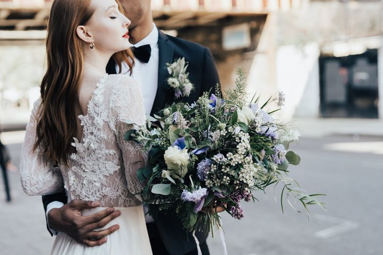 Bride in Long Sleeve Lace Wedding Dress from Morgan Davies Bridal with Groom in Black Tuxedo & Bow Tie embracing Whilst Holding a Lilac and White Wedding Bouquet
