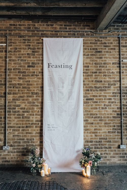 Hanging Fabric 'Feasting' Table Plan with Candles and Flowers Decorating The Footer