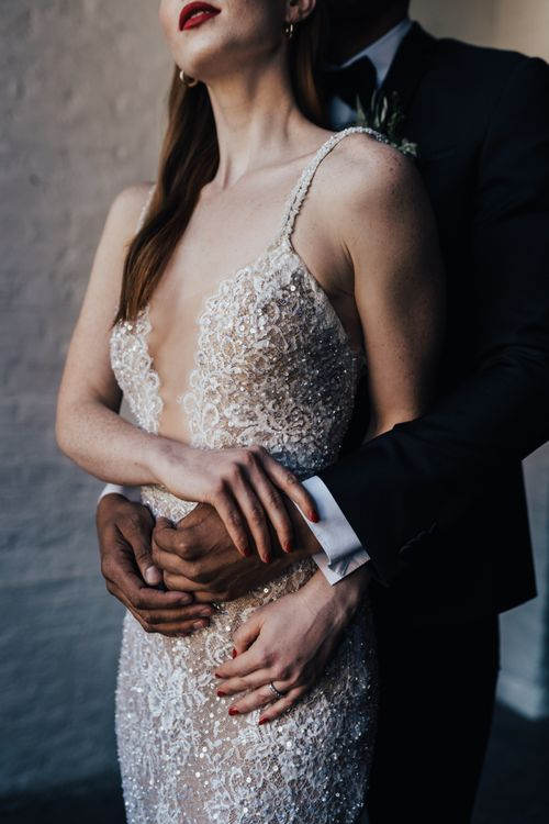 Bride in Fitted Lace Wedding Dress with Thin Straps and Low Front from Morgan Davies Bridal Embracing Her Groom in Black Tuxedo