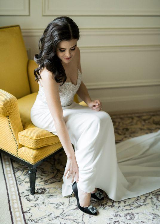 Beautiful Bride in a Tara Keely Wedding Dress Putting On Her Black Manolo Blahnik Hangisi Wedding Shoes