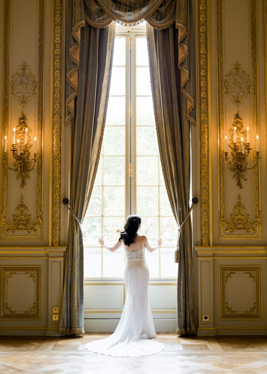Bride Standing at a Grand Window Showing off the Back of Her Tara Keely Wedding Dress