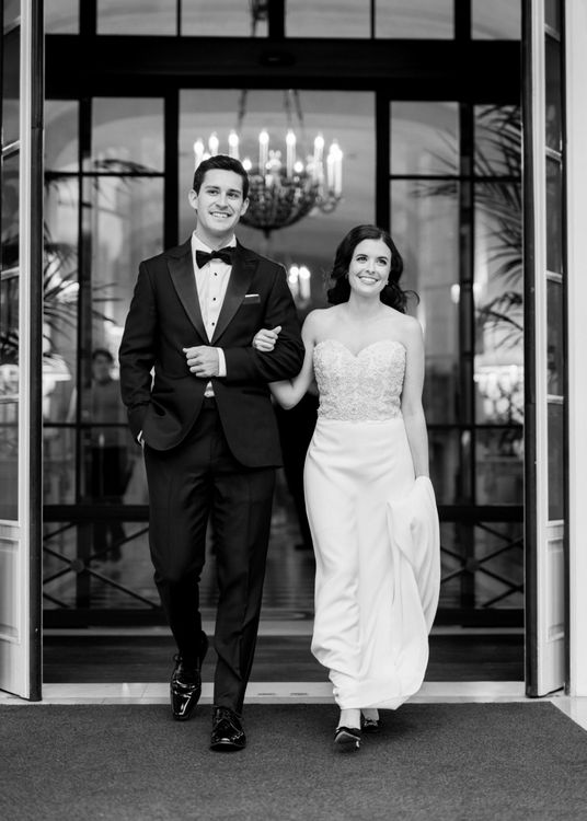 Black and White Portrait of The Bride and Groom Walking Arm in Arm