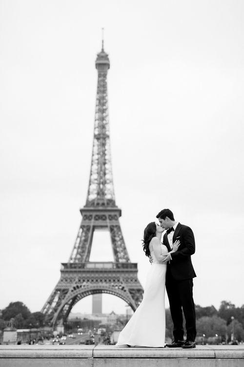 Bride in Tara Keely Wedding Dress and Groom in Black Tie Suit  Standing in Front of the Eiffel Tower
