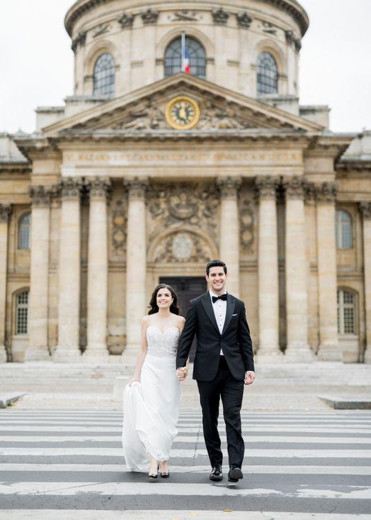 Bride in Off the Shoulder Tara Keely Wedding Dress and Groom in Black Tuxedo Walking the Streets of Paris