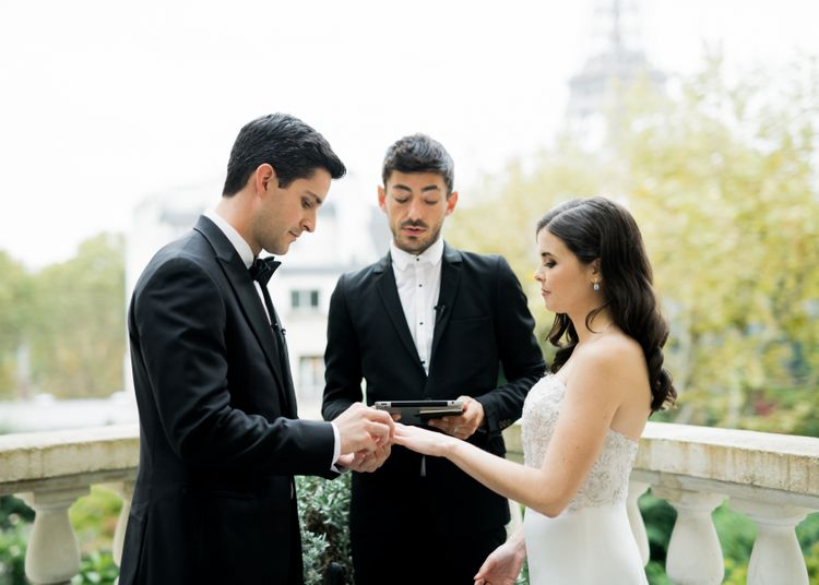 Bride and Groom Exchanging Rings on a Rooftop Terrace with Paris as their Backdrop
