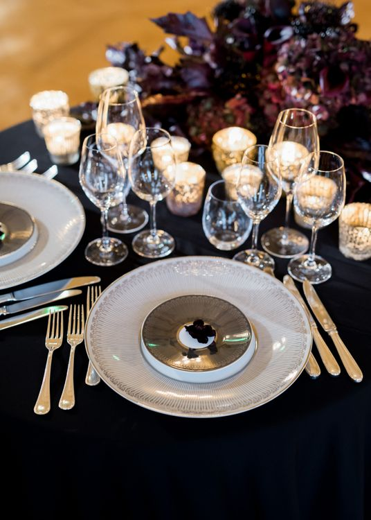 Glamorous Place Setting with Black Table Cloth, White Platter and Candle Light