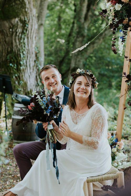 Bride and groom enjoy wedding readings at outdoor ceremony