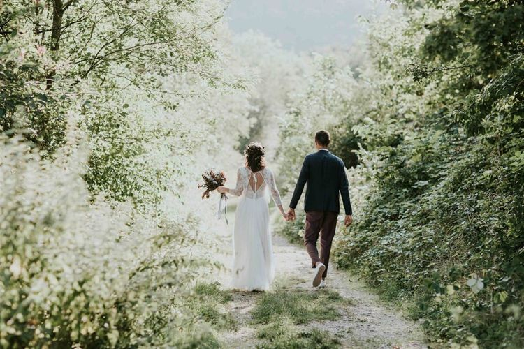 Bride and groom take a stroll through venue grounds