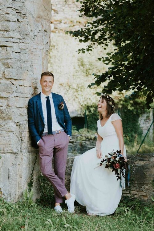 Groom wears blue wedding jacket with tie for French wedding
