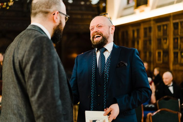 Groom in Chester Barrie Tweed Suit | Candle Lit Christmas Wedding at Gray's Inn London with Christmas Carols & Festive Wreaths | John Barwood Photography