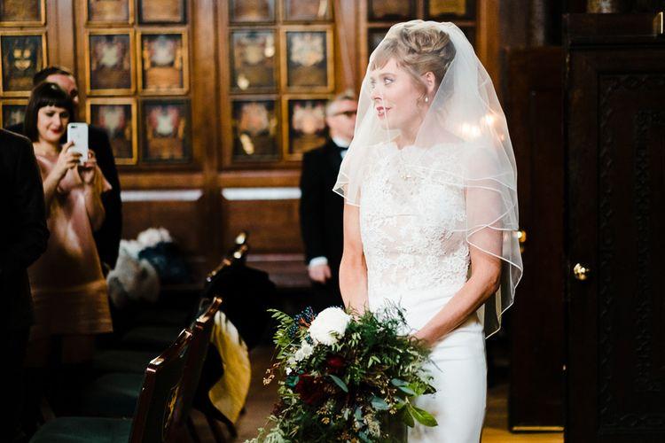 Wedding Ceremony Bridal Entrance in Lace San Patrick Gown & Veil | Candle Lit Christmas Wedding at Gray's Inn London with Christmas Carols & Festive Wreaths | John Barwood Photography