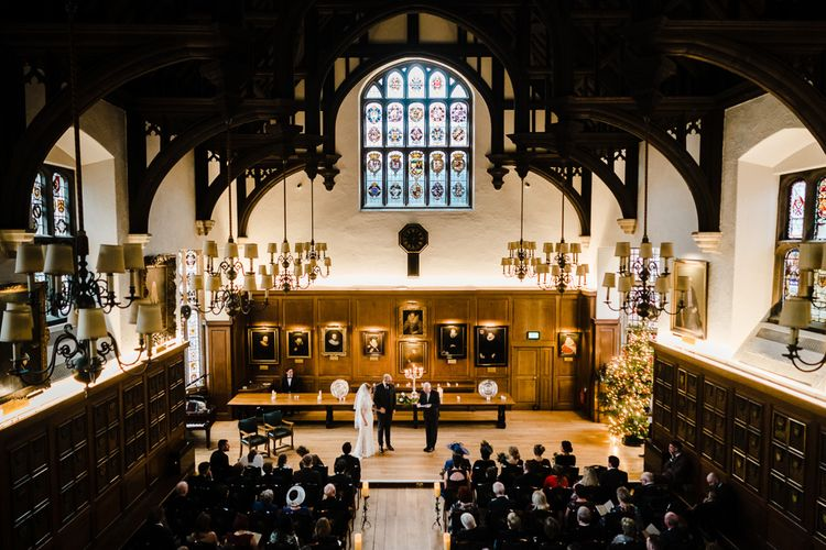 Wedding Ceremony Bride in Lace San Patrick Gown & Veil | Groom in Tweed Chester Barrie Suit | Candle Lit Christmas Wedding at Gray's Inn London with Christmas Carols & Festive Wreaths | John Barwood Photography