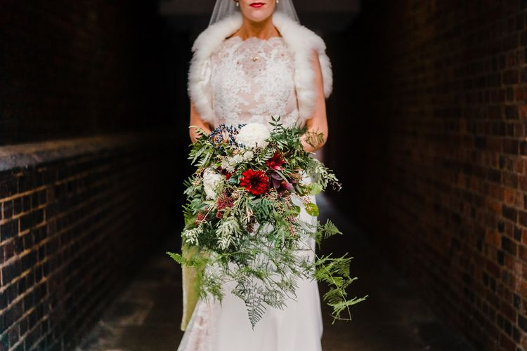Hand Tied Wedding Bouquet with Foliage, Berries & Blooms | Bride in Lace San Patrick Gown & Fur Coverup | Candle Lit Christmas Wedding at Gray's Inn London with Christmas Carols & Festive Wreaths | John Barwood Photography
