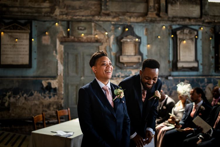 Bride in Navy Suit and Pink Tie Standing at The Asylum Altar Laughing with her Best Man