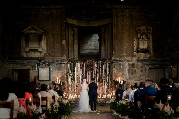 Bride and Bride Standing at The Asylum Altar with Candles and Hanging Ribbons