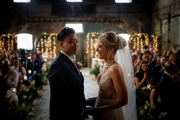 Wedding Ceremony at The Asylum with Bride in Navy Suit and Pink Tie and Bride in Romantic Flora Mila Wedding Dress Holding Hands at the Altar