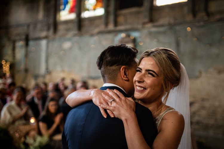 Wedding Ceremony at The Asylum with Bride in Navy Suit and Pink Tie and Bride in Romantic Flora Mila Wedding Dress Embracing at the Altar