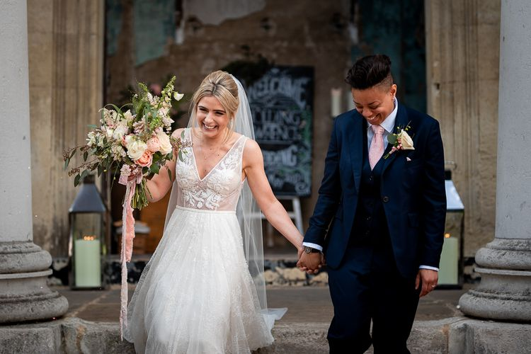 Bride in Navy Suit and Pink Tie and Bride in Romantic Flora Mila Wedding Dress  Exiting The Wedding Ceremony as Mrs & Mrs