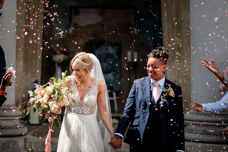 Confetti Moment with Bride in Navy Suit and Pink Tie and Bride in Romantic Flora Mila Wedding Dress