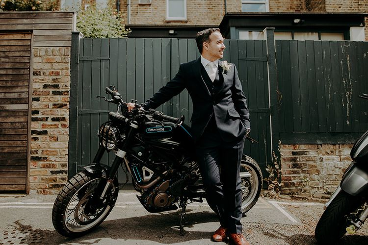 Groom in Cad & The Dandy Suit Standing Next to a Motorbike